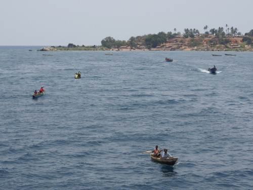 several small boats arriving from the village